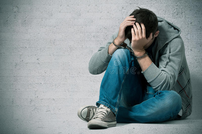 Adolescente arrestado con las manillas imagenes de archivo