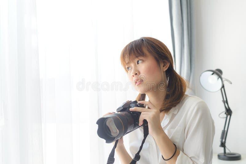Adolescente asiático con la cámara digital en casa fotografía de archivo libre de regalías