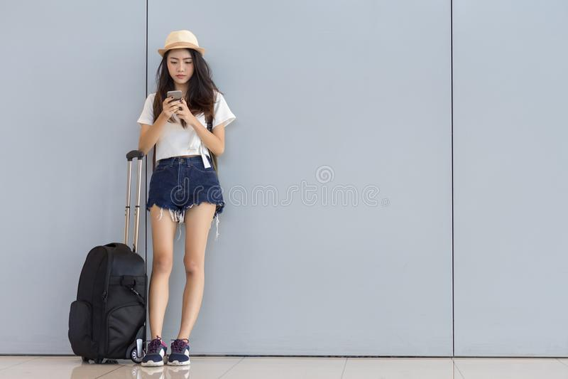 Adolescente asiático de la mujer que usa smartphone en el aeropuerto foto de archivo