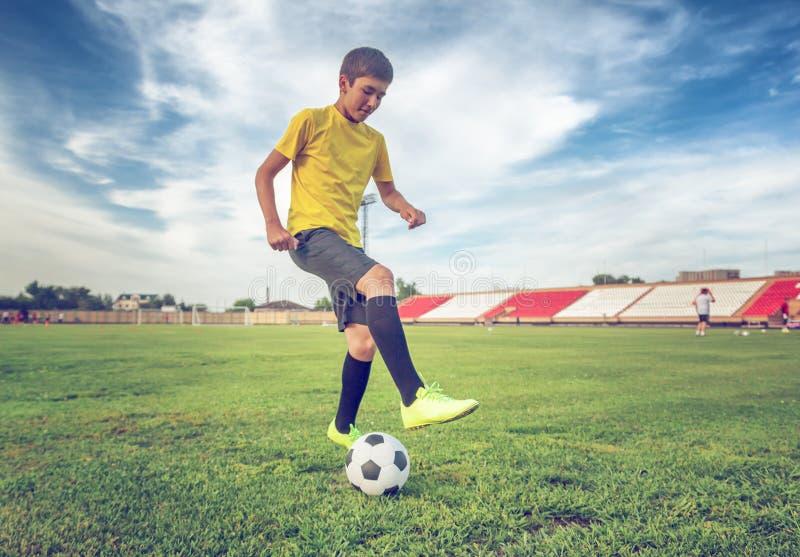 Adolescente asiático del muchacho que juega al fútbol en el estadio, deportes, outd imágenes de archivo libres de regalías