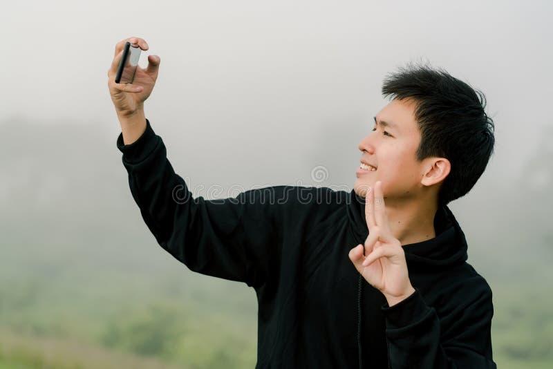 Adolescente asiático do menino que veste o suporte preto da roupa do inverno para tomar imagens do senhor mesmo com um telefone c imagem de stock