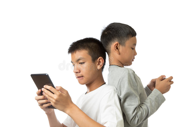 Adolescente asiático e seu irmão na tabuleta e no smartphone imagem de stock royalty free