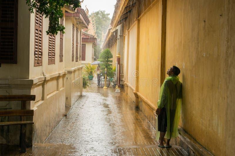 Adolescente asiático esperando a chuva da monção para parar imagem de stock