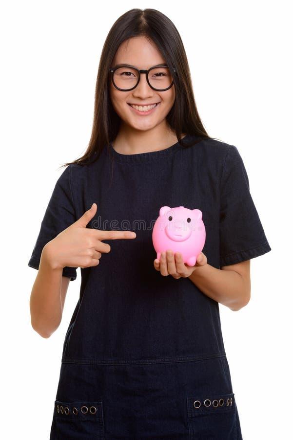Adolescente asiático feliz novo que sorri ao apontar o dedo e imagens de stock