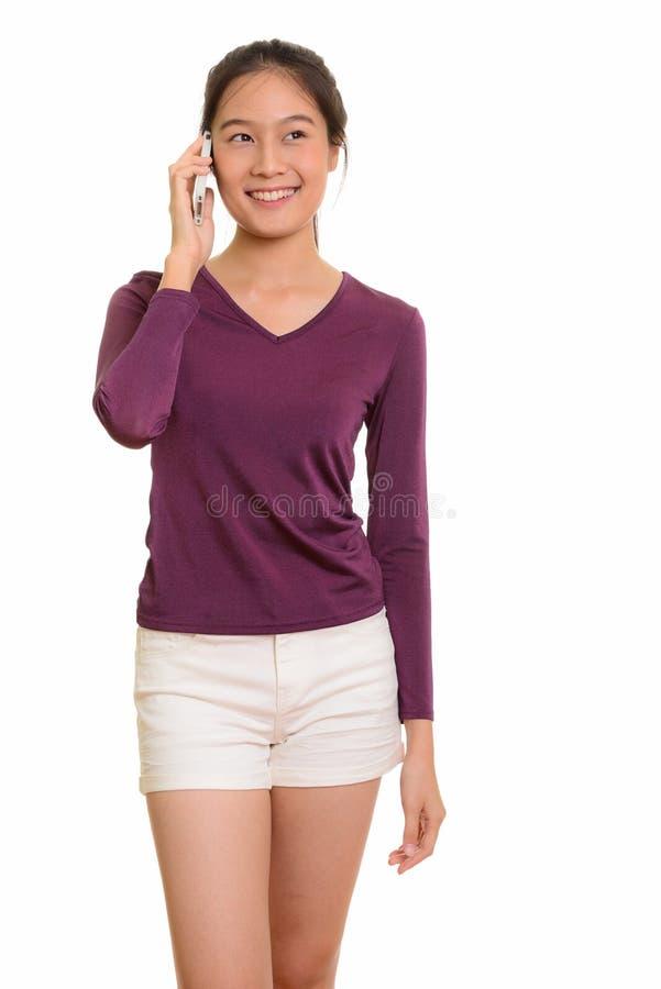 Adolescente asiático feliz novo que sorri e que fala no pho móvel fotografia de stock