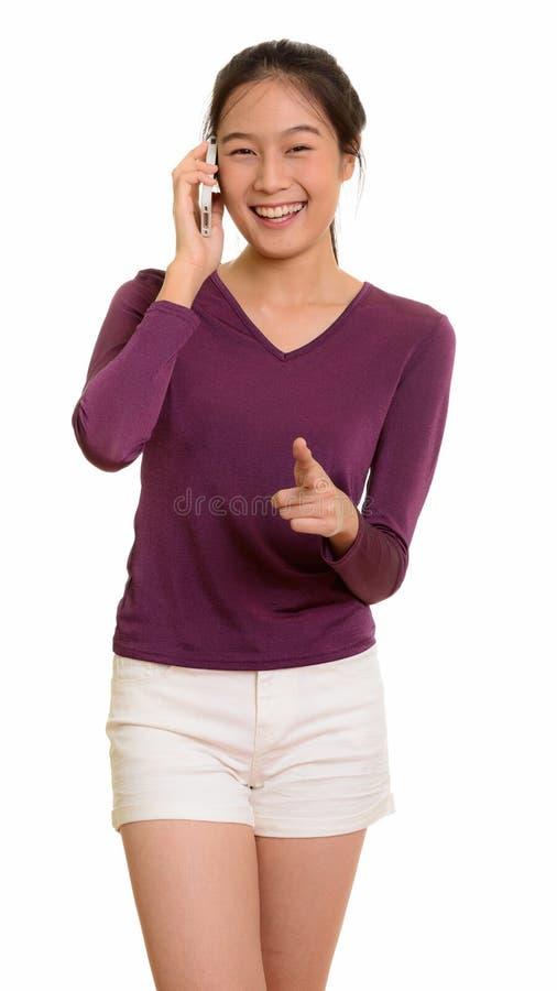 Adolescente asiático feliz novo que sorri e que fala no pho móvel foto de stock