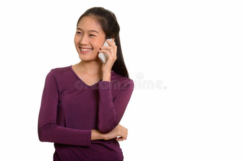 Adolescente asiático feliz novo que sorri e que fala no pho móvel fotos de stock