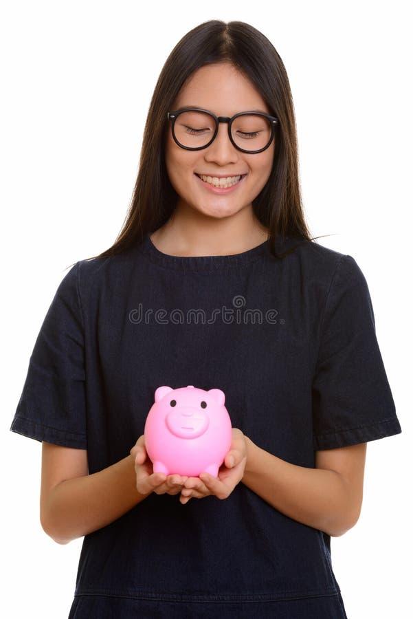 Adolescente asiático feliz novo que sorri e que guarda o mealheiro fotos de stock royalty free