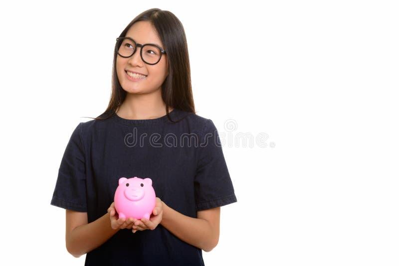 Adolescente asiático feliz novo que sorri e que guarda o wh do mealheiro fotografia de stock