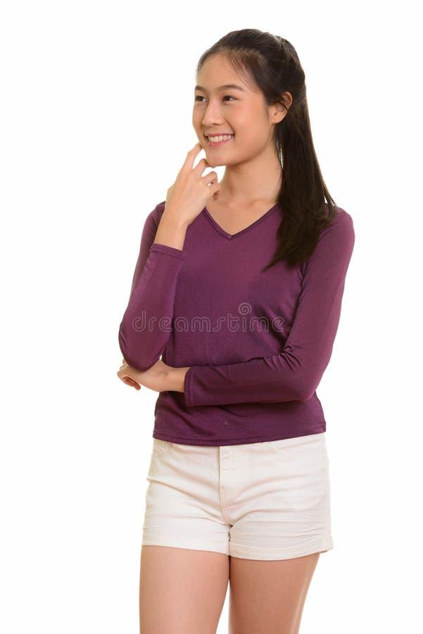 Adolescente asiático feliz novo que sorri e que pensa fotografia de stock royalty free