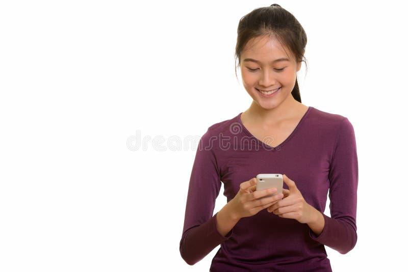 Adolescente asiático feliz novo que sorri e que usa o telefone celular imagens de stock royalty free
