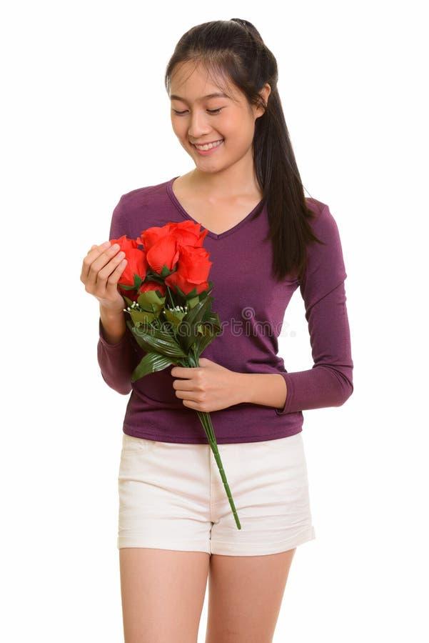 Adolescente asiático feliz novo que sorri guardando as rosas vermelhas f pronto imagens de stock