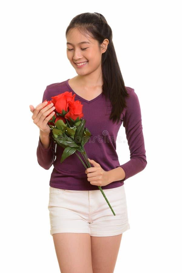 Adolescente asiático feliz novo que sorri guardando as rosas vermelhas f pronto imagem de stock