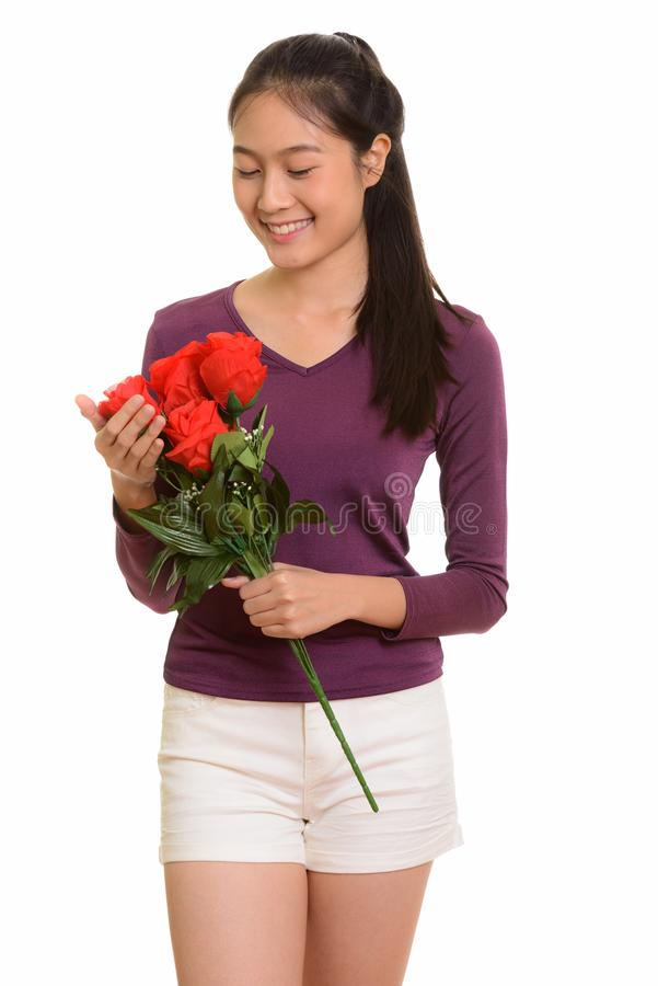 Adolescente asiático feliz novo que sorri guardando as rosas vermelhas f pronto fotos de stock royalty free