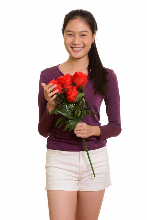 Adolescente asiático feliz novo que sorri guardando as rosas vermelhas f pronto imagem de stock royalty free