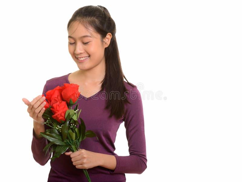 Adolescente asiático feliz novo que sorri guardando as rosas vermelhas f pronto imagens de stock royalty free