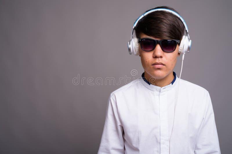 Adolescente asiático joven que escucha la música contra backgrou gris foto de archivo libre de regalías