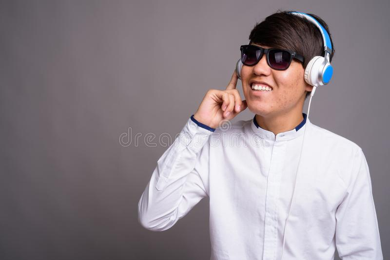 Adolescente asiático joven que escucha la música contra backgrou gris fotos de archivo