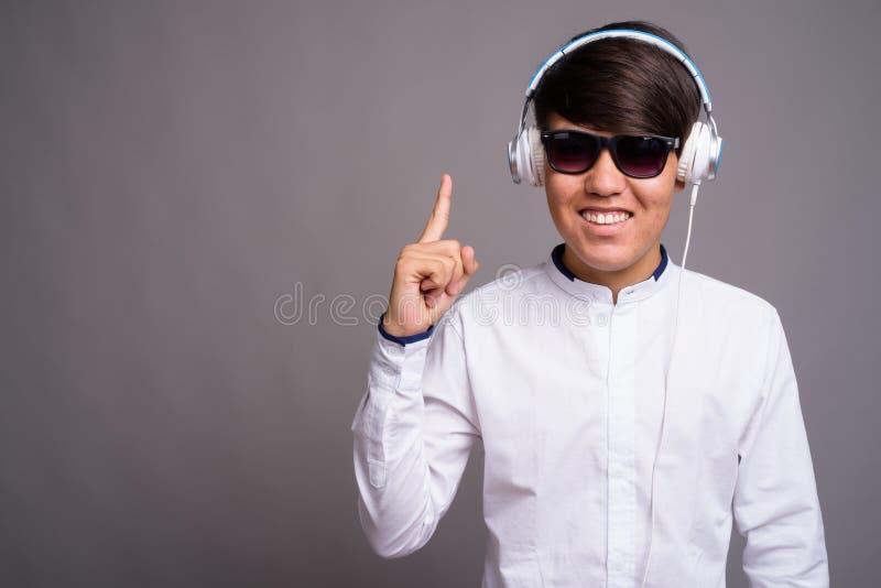 Adolescente asiático joven que escucha la música contra backgrou gris imagenes de archivo