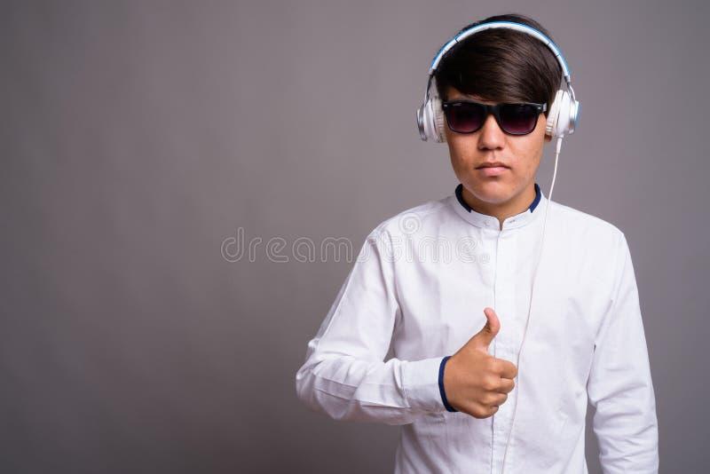Adolescente asiático joven que escucha la música contra backgrou gris fotografía de archivo libre de regalías