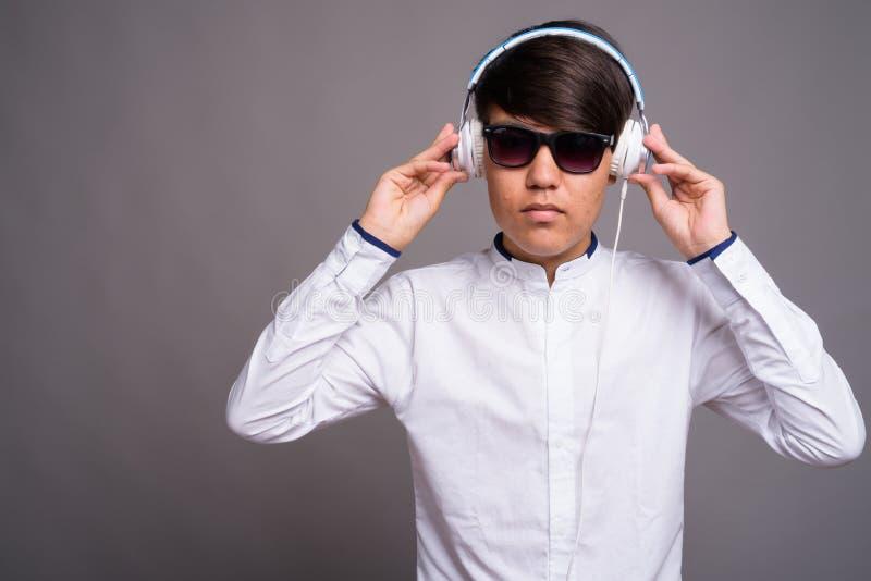 Adolescente asiático joven que escucha la música contra backgrou gris imagen de archivo