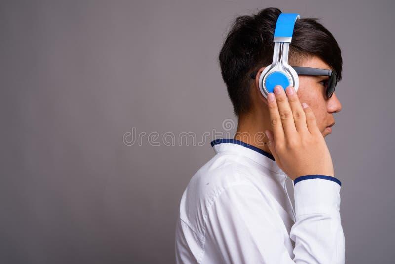 Adolescente asiático joven que escucha la música contra backgrou gris fotos de archivo libres de regalías
