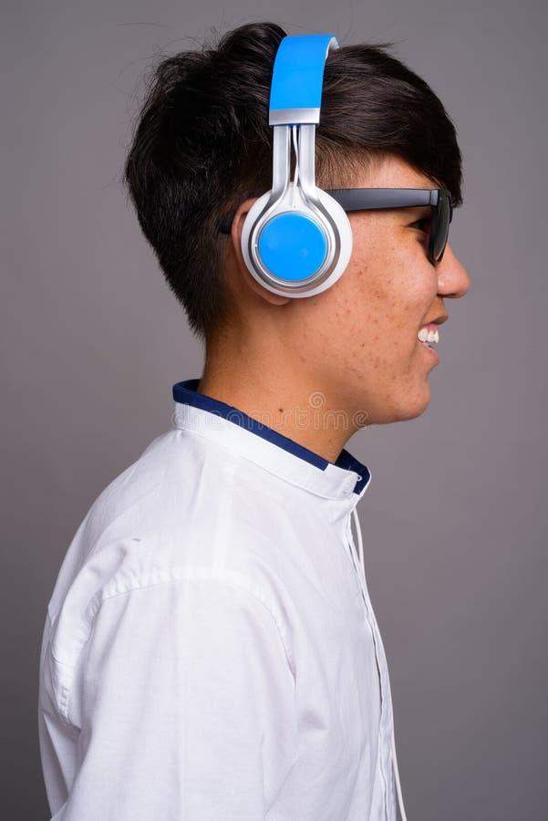 Adolescente asiático joven que escucha la música contra backgrou gris foto de archivo
