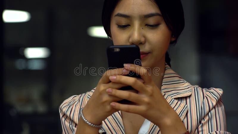 Adolescente asiático joven que usa un smartphone para comprar productos en línea imagenes de archivo