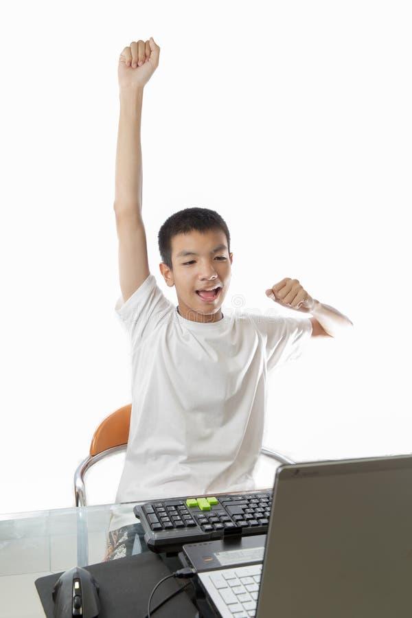 Adolescente asiático que usa el ordenador con gesto de la victoria imagenes de archivo