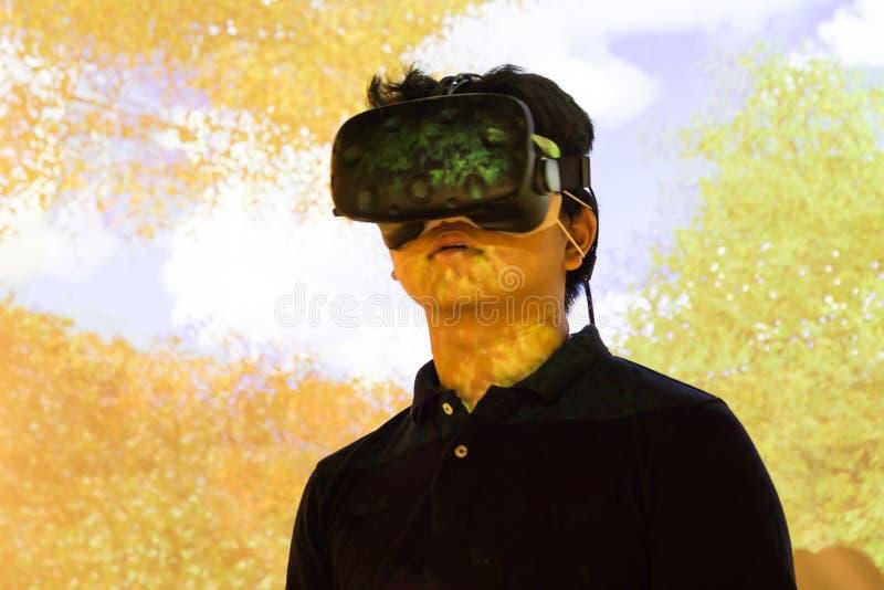 Adolescente asiatico che avverte il gad di spettacolo di realtà virtuale di VR immagine stock
