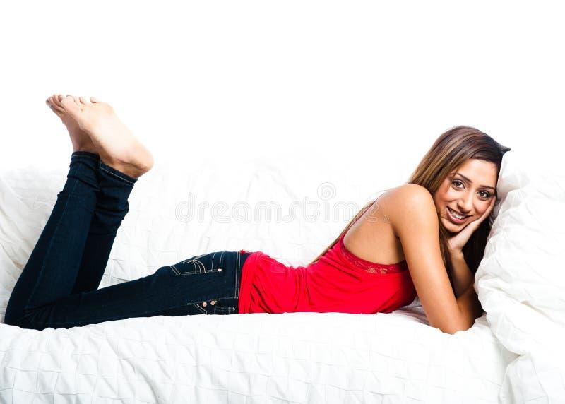 Adolescente asiatico sul sofà, piedi in aria immagini stock