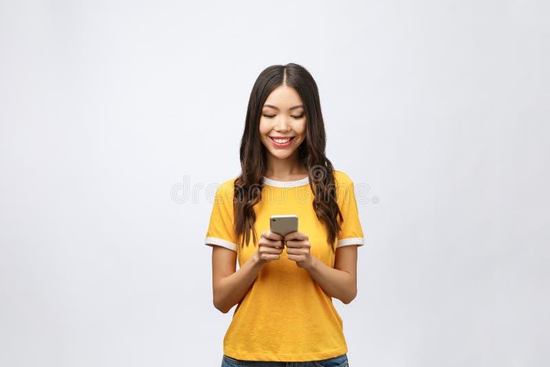 Adolescente asiatique attirante regardant son écran de téléphone portable avec le visage joyeux, sur le fond blanc pour l'espace  photo stock
