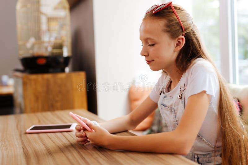 Adolescente atractivo con el mensaje largo rubio de la lectura del pelo en el teléfono fotografía de archivo libre de regalías