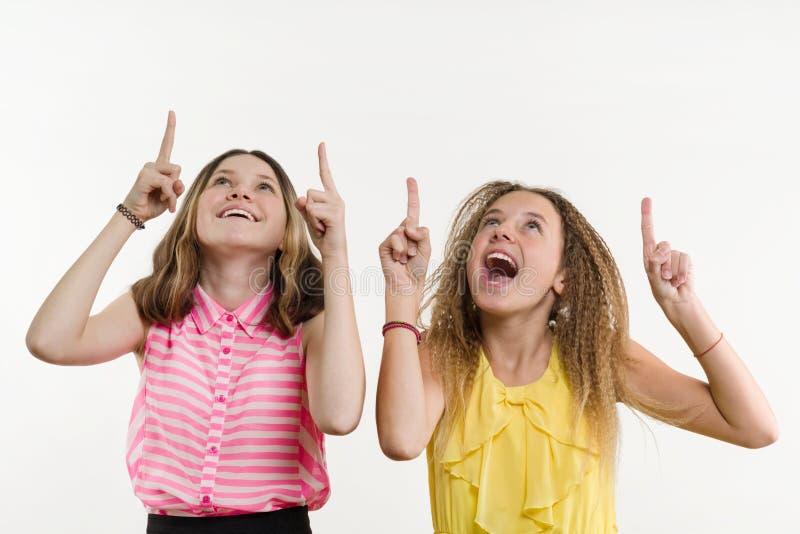 Adolescente atrativo do positivo dois que aponta seu indicador acima fotos de stock royalty free