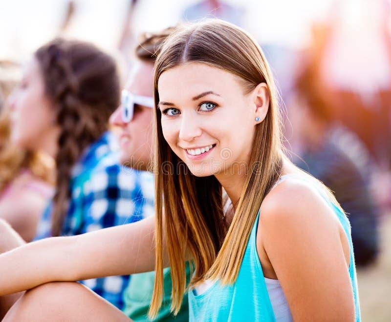 Adolescente au festival de musique d'été, se reposant au sol photo stock