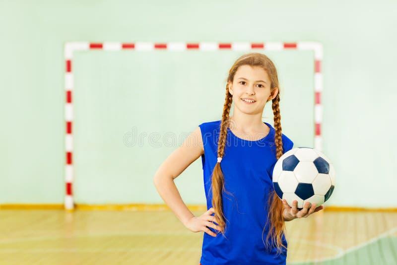 Adolescente avec du ballon de football dans le gymnase d'école photographie stock