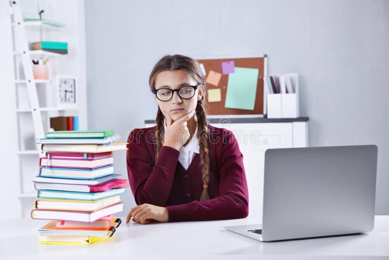 Adolescente avec la pile des livres et de l'ordinateur portable se reposant au bureau dans une salle de classe image libre de droits