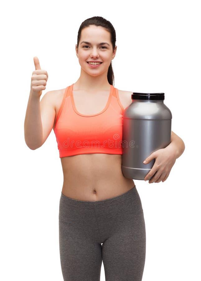 Adolescente avec le pot de protéine montrant des pouces  photos stock
