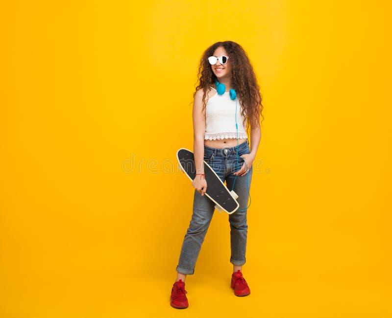 Adolescente avec le sourire de planche à roulettes image libre de droits