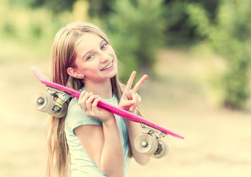Adolescente avec le sourire rose de planche à roulettes images stock