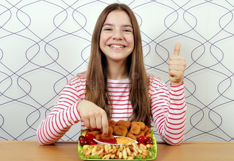 Adolescente avec les p?pites et le pouce de poulet savoureux  photos stock