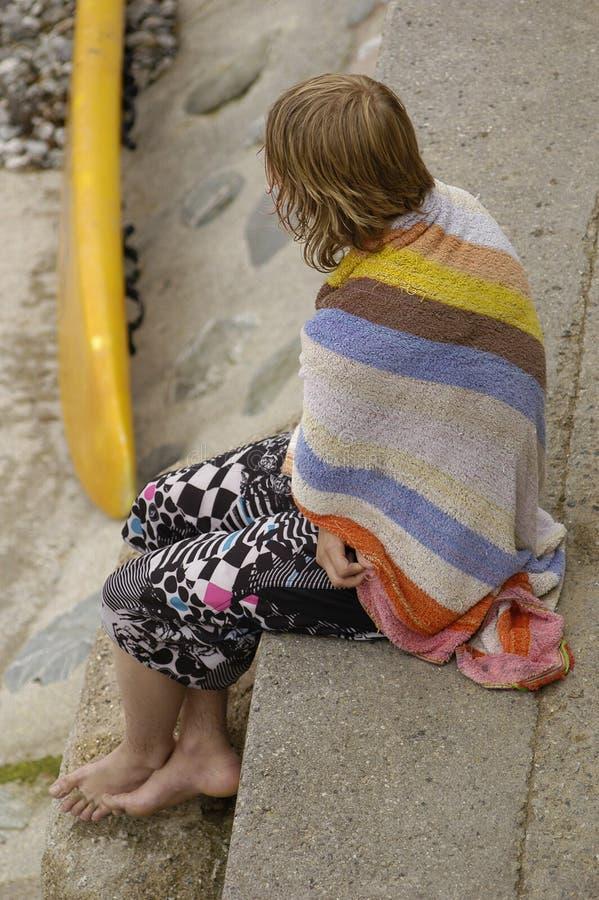 Adolescente avvolto in asciugamano sulla spiaggia   fotografie stock