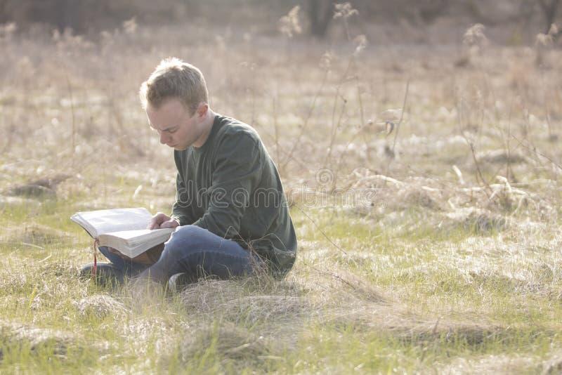 Adolescente in bibbia aperta della lettura del campo fotografia stock