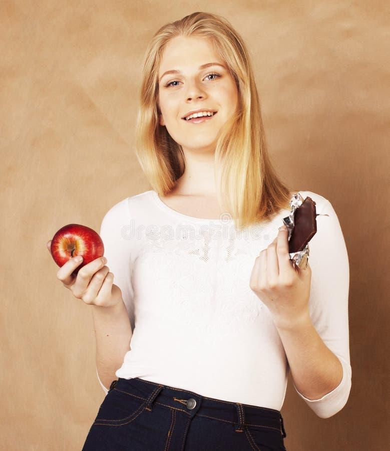 Adolescente biondo di giovane bellezza che mangia sorridere del cioccolato, scelta fra il dolce e mela fotografia stock libera da diritti