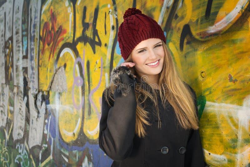 Adolescente biondo sveglio con il cappello contro la parete dei graffiti fotografie stock