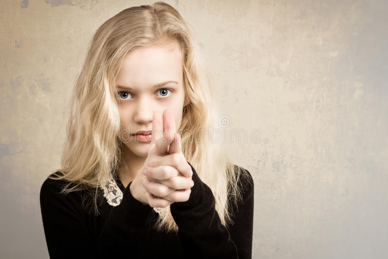 Adolescente blonde dirigeant l'arme à feu de doigt à l'appareil-photo photo stock