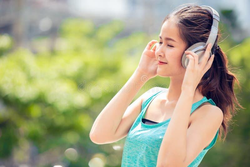 Adolescente bonito asiático com os fones de ouvido sem fio que sorriem para apreciar a música exterior imagens de stock royalty free