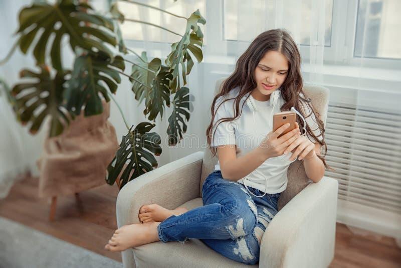 Adolescente bonito com música de escuta do smartphone e dos fones de ouvido imagem de stock royalty free
