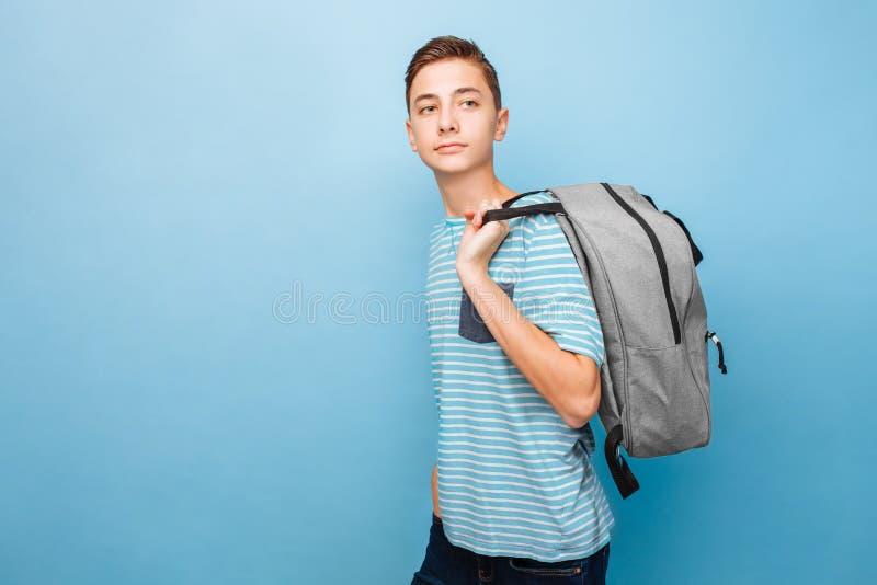 Adolescente bonito com uma pasta, em um fundo azul foto de stock royalty free