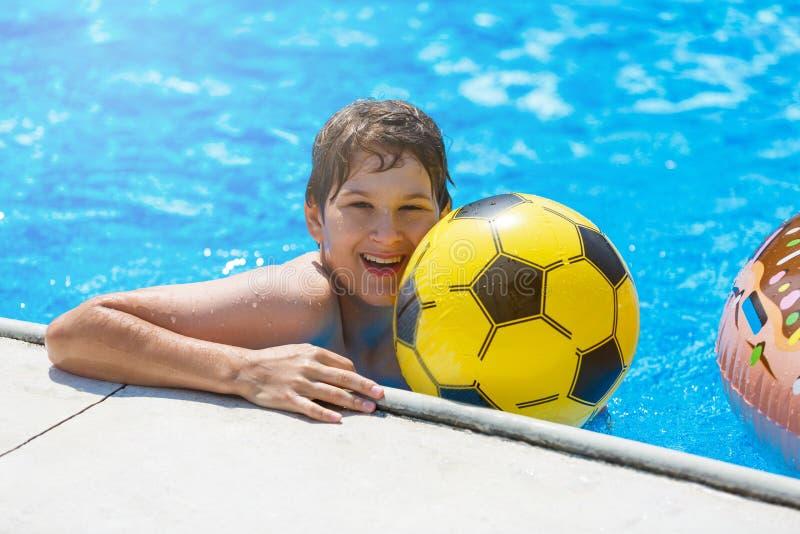 Adolescente bonito feliz do rapaz pequeno na piscina Jogos ativos na água, férias, conceito dos feriados Filhós do chocolate foto de stock royalty free